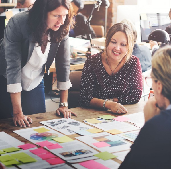 A group of people happily collaborating inside a studio environment over design layouts.