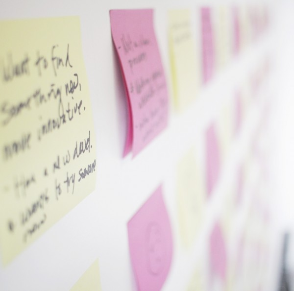 Rows of post-it notes up-close on a wall.